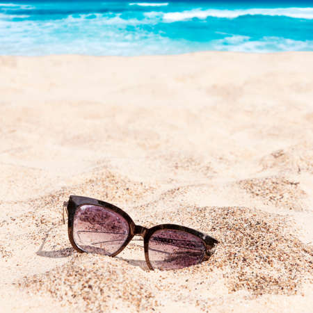 Old lost abandoned sunglasses on beach sand with turquoise Caribbean ocean in background in bright summer day. Tropical summer vacation concept