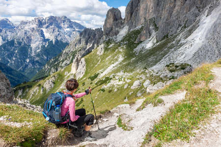 Mountain hiking with woman sitting to rest and looking at scenic landscape in summer day, breathtaking scenery of Italian Dolomite Alps Banque d'images - 137180862