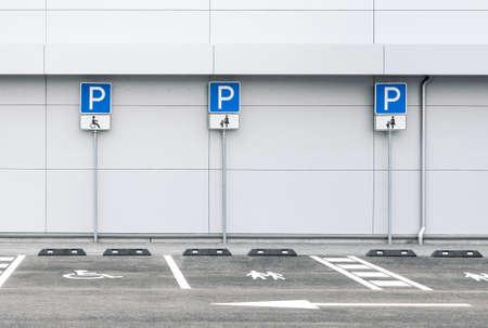 Estacionamiento de automóviles vacío en un supermercado con lugares de estacionamiento para familias y discapacitados, señales de tráfico de estacionamiento público