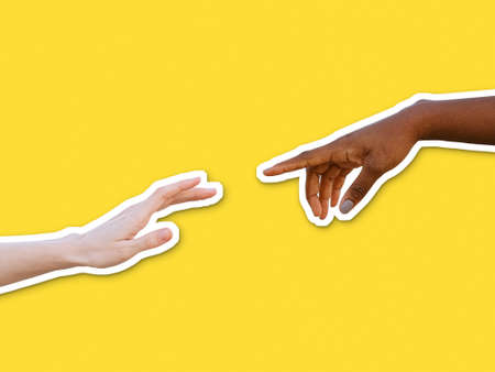 Black and white hands reaching towards each other on yellow background. Friendship and racial respect concept in collage cut out style