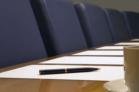Boardroom -  close-up of a conference room showing a row of chairs, a table, part of a coffee cup, documents (blank) and a pen resting on a piece of paper. Sharp focus on the pen. photo
