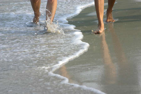 A Walk On The Beach - An image of a couples legs walking side by side along the waters edge