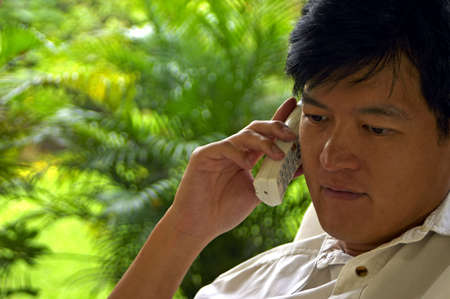 confiding: Asian Male Listening Intently On The Phone