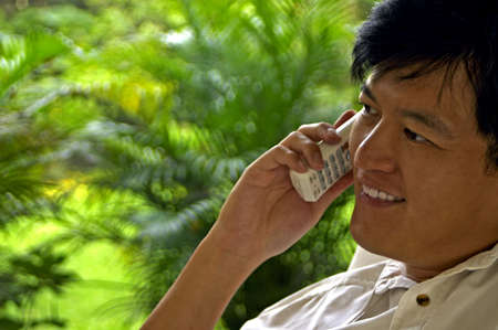 confide: Asian Male Chatting Happily On The Phone Stock Photo