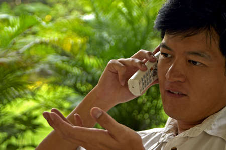 confiding: Asian Male Talking On The Phone