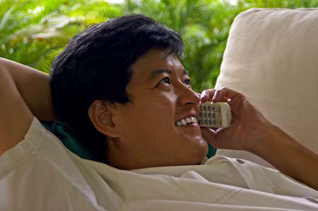 Asian Male Relaxed On The Phone With A Friend Stock Photo