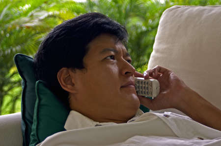 confiding: Asian Male Listening On The Phone With A Concerned Look Stock Photo