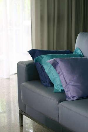 blue leather sofa: Un divano in pelle blu e cuscini in stile minimalista