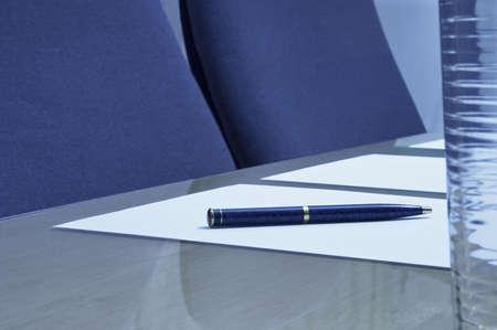 Close-up of a Boardroom showing a pen on a piece of paper with a glass of water in the foreground. sharp focus on the pen.