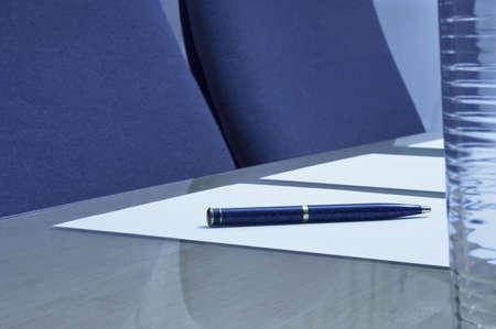 atender: Primer de una sala de reuni�n que demuestra una pluma en un pedazo de papel con un cristal de agua en el foco agudo del primero plano en la pluma.