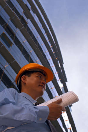 way out: Asian male in a hard-hat holding some floor plans on his way out to a construction site Stock Photo