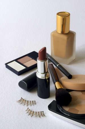 An assortment of womens make-up -  foundation, powder, lipstick, eyeshadow, lip liner, cheek brush & fake eyelashes Stock Photo