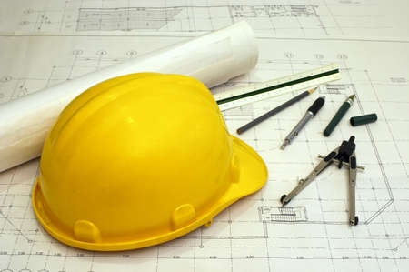 Floor plans and a hard hat with various drawing tools - scale ruler, compass, pen and pencil Stock Photo