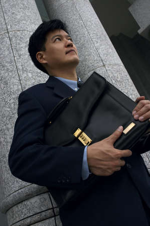 Asian Man in a Business Suit Holding a Briefcase Expressing Confidence and Determination