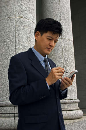 Asian Man In A Business Suit with A PDA (Vertical Format)