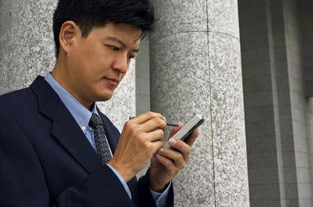 organise: Asia hombre en un traje de negocios con una PDA (Formato horizontal)