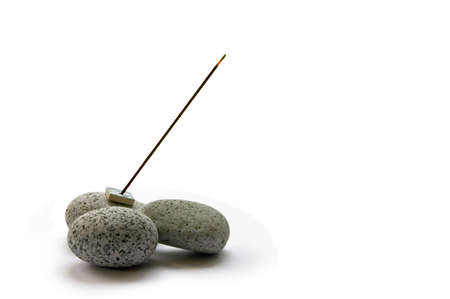 ладан: A stick of burning Japanese incense on some smooth pebbles