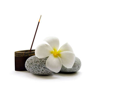 A stick of fragrant Japanese incense, some smooth pebbles and a frangipani flower photo