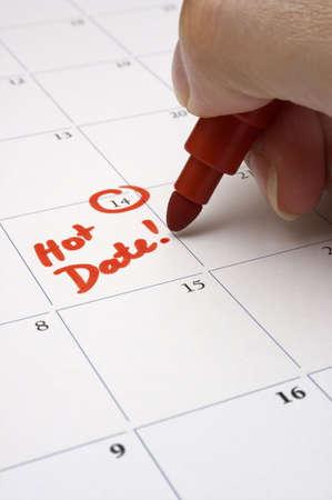 persona escribiendo: Para reservar una fecha - Una persona escribiendo la cita para una fecha en el calendario. Profundidad de campo - se centr� en las palabras andamp, quot, Hot Dateandamp, quot,.