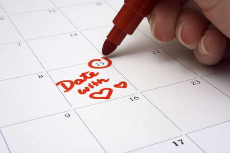 Making A Date - A person writing down the appointment for a date with a loved one on the calendar. Shallow depth-of field - focused on the words andamp,quot,Date withandamp,quot,. photo