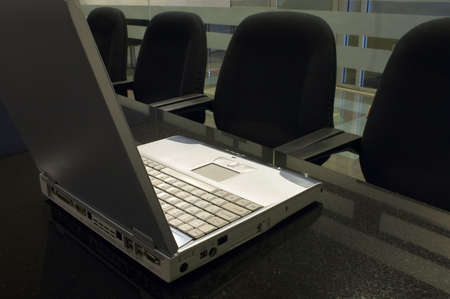 Office Interior 1 - A laptop computer on a black granite table in a conference room. Stock Photo