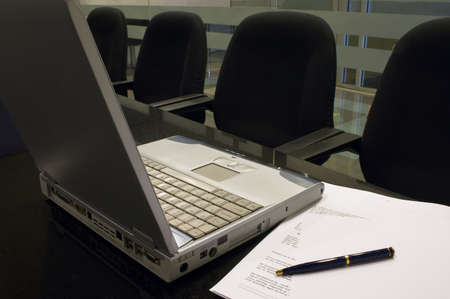 Office Interior 2 - A laptop computer, some documents, blank paper and a pen on a black granite table in a conference room