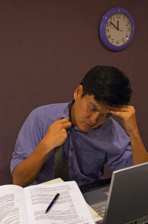 Frustrated at Work - A man working late is feeling stressed and loosens his tie. It is close to midnight and he is still working at his computer in his cubicle. Stock Photo