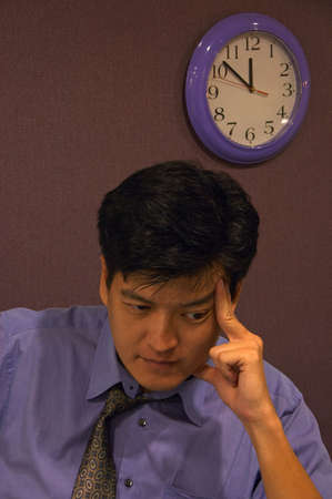 working overtime: Deadlines - An employee working overtime on a deadline thinks hard for a solution. Stock Photo