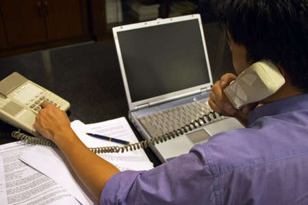 Making A Business Call - A man dialing the phone at his work desk.