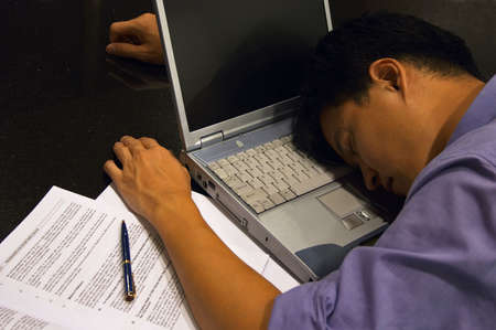 Totally Exhausted - A man burnt out & sleep-deprived from work falls asleep in front of his computer. Stock Photo