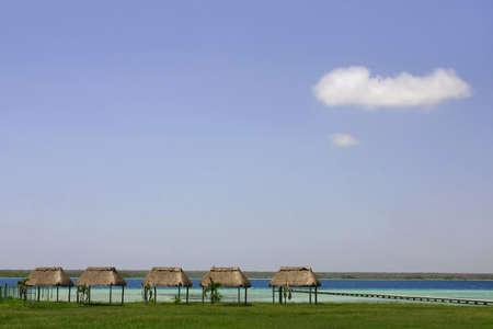 shores: Four palapas on the shores of Lake Bacalar, Mexico