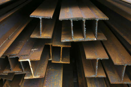 corrode: Metal Beams - Close-up of rusty steel beams stacked at a construction site