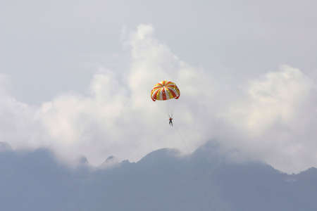 vacationer: Male vacationer parasailing high in the sky above the mountains of Langkawi Island, Malaysia. The speedboat pulling him is omitted. Stock Photo