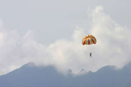 parasailing: Male vacationer parasailing high in the sky above the mountains of Langkawi Island, Malaysia. The speedboat pulling him is omitted. Stock Photo