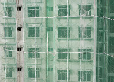 netting: Appartementencomplex in aanbouw met steigers en groen verrekening op de buitenkant Stockfoto
