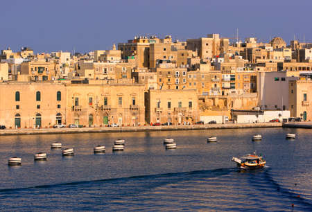 cruising: Tour boat cruising the Dockyard Creek against the backdrop of Vittoriosa in Malta