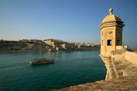 cruising: The Vedette in Senglea, Malta, overlooking a tourist schooner cruising along the Grand Harbour with Valletta in the background