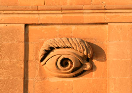 malta cities: Detail of the eye carving on the Vedette glowing from the red sunset in Senglea, one of the Three Cities of Malta Stock Photo