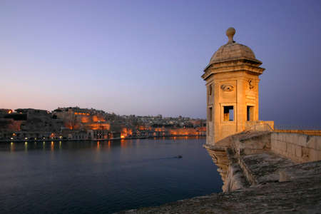 The Vedette during dusk in Senglea, one of the Three Cities against the backdrop of Grand Harbour and Valletta in Malta
