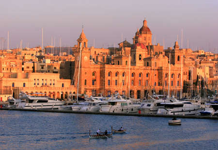 Traditional wooden Dghajsa boats against the backdrop of Vittoriosa Wharf and the buildings of Vittoriosa, one of the Three Cities of Malta, during sunset Stock Photo