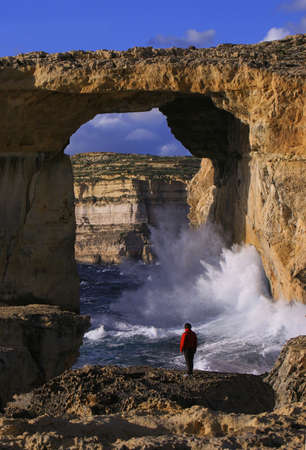 Tourist taking in the dramatic view of Azure Window, a natural hole in the coastal cliffs of Gozo Island, Malta
