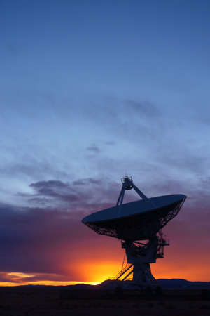 Silhouette of a radio telescope at the Very Large Array (VLA) in New Mexico, USA, at sunset photo