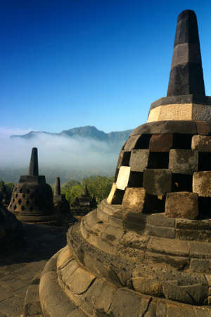 Stupas on the upper terraces of the ancient temple of Borobudur, Indonesia, on a misty morning