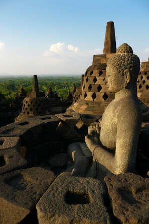 stupa one: One of the many Buddha statues sitting inside a stupa on the top terraces of the ancient temple of Borobudur, Indonesia