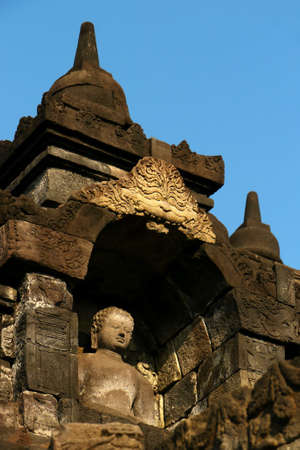One of the many Buddha statues sitting inside an alcove in the ancient temple of Borobudur,Java, Indonesia