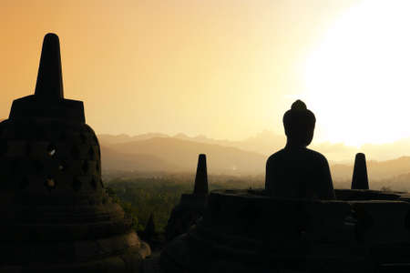 One of the many Buddha statues and stupas on the top terraces of the temple of Borobudur, set against the hills  Plenty of copy space at the top  Stock Photo