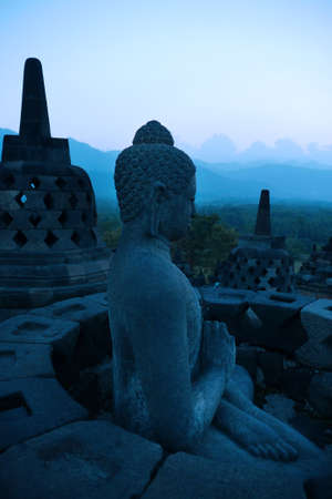 Statue of Buddha and stupas on the top terrace of the temple, set against the layered hills at dusk   Stock Photo