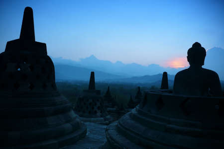 One of the many Buddha statues and stupas on the top terraces of Borobudur, Indonesia, set against the layered hills at dusk  The mood is mysterious at this ancient temple at dusk