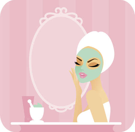 Young woman with a towel over her hair applying a facial mask in front of a vanity mirror On the counter are some tools and ingredients for making a homemade organic mask