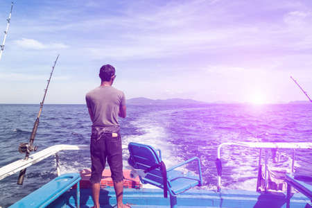 Trolling fishing boat rod and fisherman was fishing in deep blue ocean sea wake with retro over light